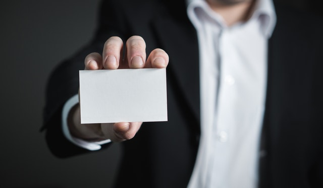Image of a businessman holding a blank business card - he still needs a business name.