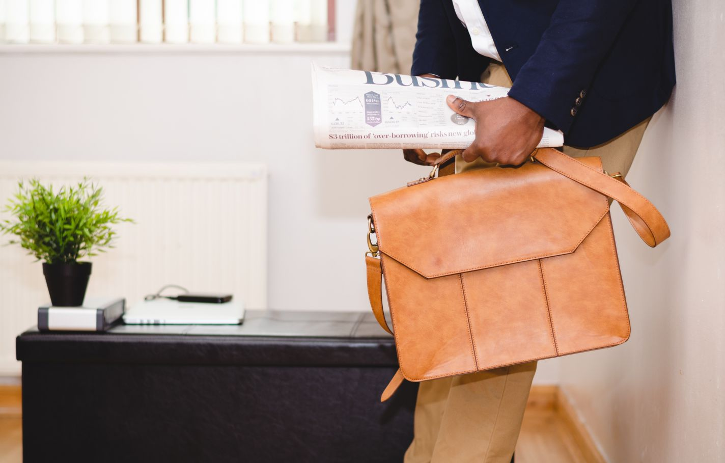 An industrious entrepreneur or business owner leaning against an office wall with a business newspaper in hand along with a tan briefcase.