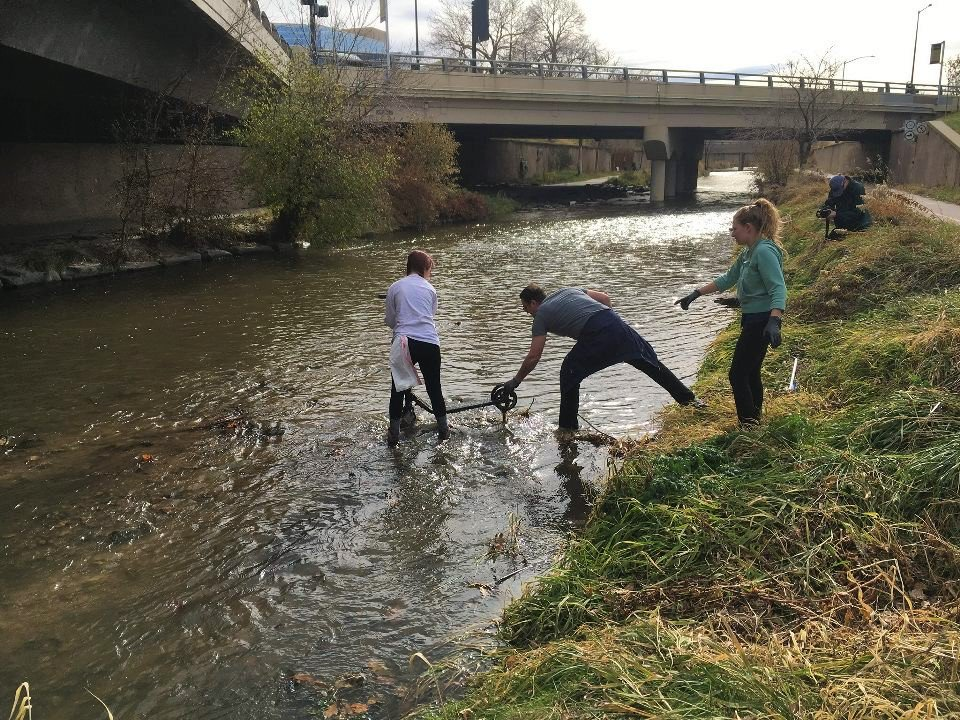 Attorney, Jeff Pote, helping to remove a e-scooter from Cherry Creek in Denver, Colorado as part of a trash cleanup for America Recycles Day organized the volunteers of Auraria Sustainable Campus Program.