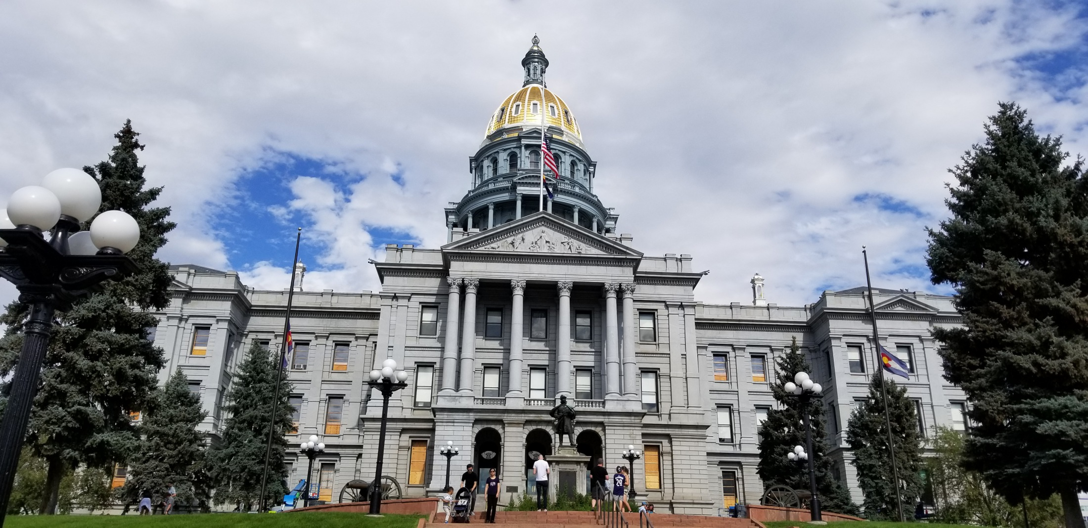 The Colorado State Capitol building with its gold dome glistening under a partly cloudy blue Colorado sky.
