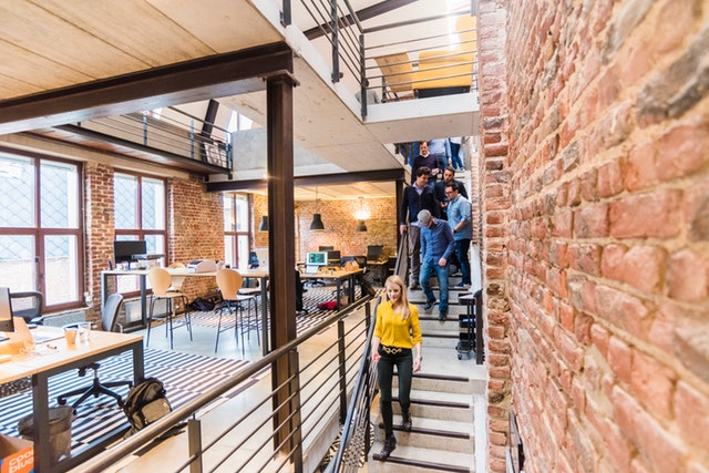 Modern office with stairs along a brick wall as several young entrepreneurs descend past open workspaces.