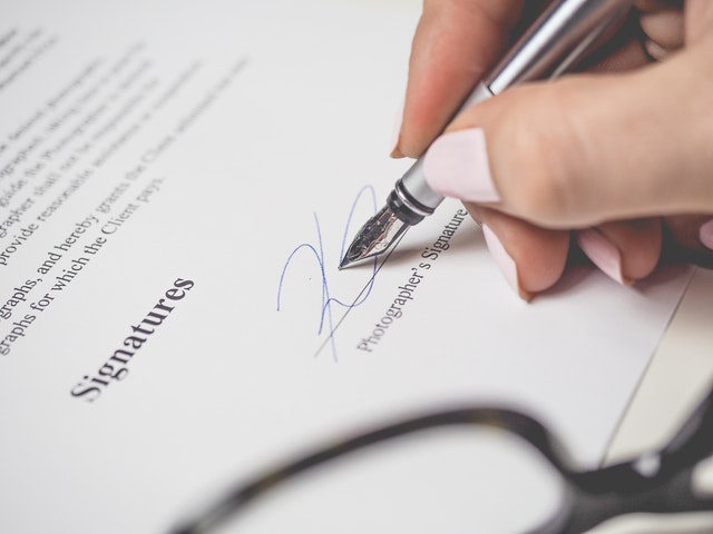 a close-up image of a business woman's hand signing a contract with a silver pen.