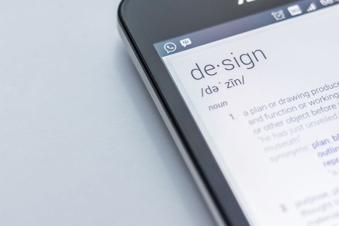 A black smartphone displaying the dictionary result for the word 'design' indicating that it's a noun and the definition starts 'a plan or drawing...'.
